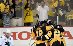 Penguins teammates congratulate Nick Bonino after scoring the game-winning goal over the Sharks in Game 1 of the Stanley Cup final Monday at Consol Energy Center.