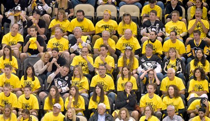 Penguins fans — except for some, including Claudette Dagorn (third row from the bottom, second seat from the left) — wear free yellow shirts distributed by the team