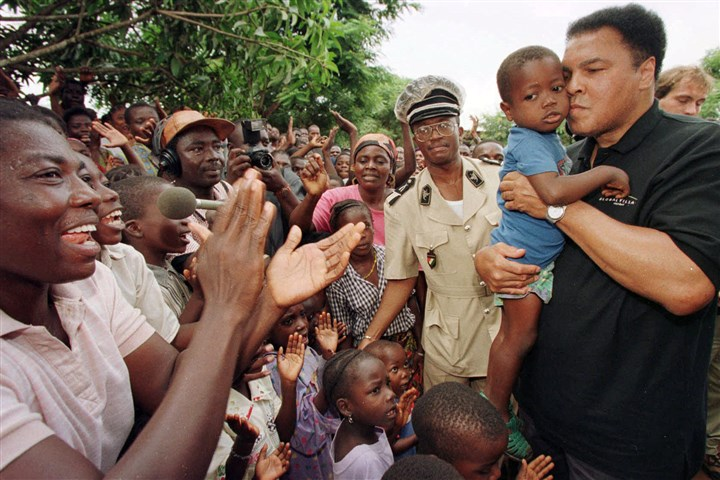 91t00kw2-30 In this Aug. 20, 1997 file photo, former heavyweight boxing champion Muhammad Ali kisses a Liberian orphan while residents cheer Ali's arrival at an orphanage for Liberian refugees in San Pedro, Ivory Coast.