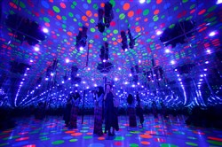 Visitors take photographs inside Infinity Dots Mirrored Room by artist Yayoi Kusama at The Mattress Factory in June.