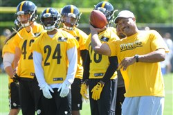 Steelers defensive backs coach Carnell Lake toss a pass during the team's practice Thursday on the South Side.