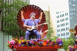 A guitarist with Squonk Opera performs on a mounted stage decorated with bright flowers.