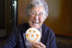 Norma Bauerschmidt, 91 of Presque Isle , Michigan,  holds up her favorite Smiley cookie, in their RV in the Bear Run Campgrounds near Portersville in June.