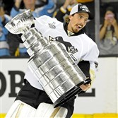 Goaltender Marc-Andre Fleury carries the Stanley Cup after the Penguins defeated the Sharks in Game 6 of the Stanley Cup final.