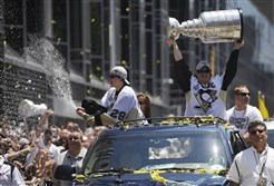 Sidney Crosby hoists the Stanley Cup and Marc-Andre Fleury sprays champagne into the air during the Penguins victory parade in Downtown Pittsburgh in June 2009, the last time the team won the Cup.