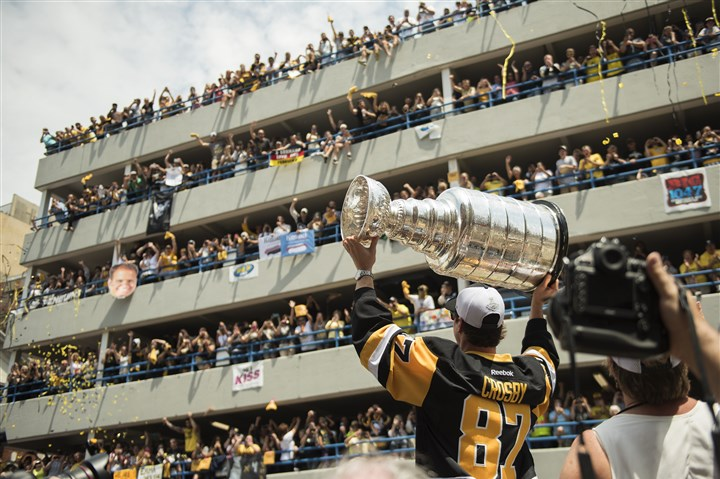20160615hmnPensVictoryParade-2 Fans cheer from parking garage as Sidney Crosby lifts the Stanley Cup over his head during Wednesday victory parade down the Boulevard of the Allies.