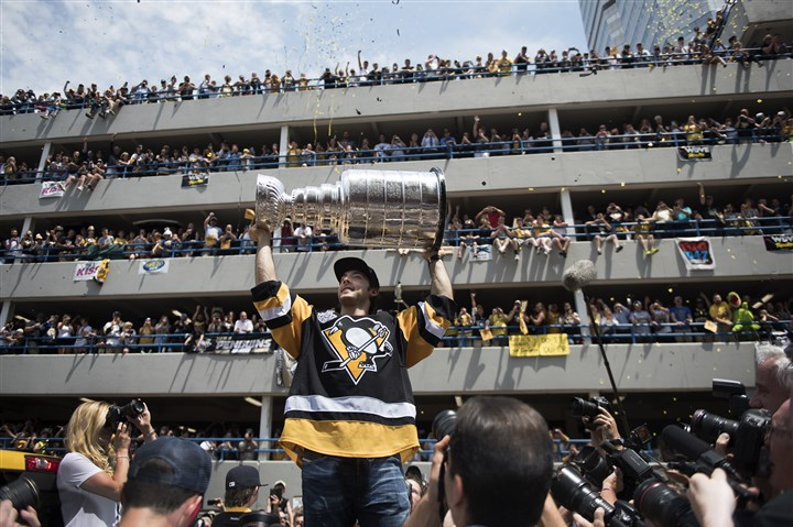 20160615hmnPensVictoryParade-5 Fans cheer from a parking garage as Kris Letang raises the Stanley Cup during the parade down the Boulevard of the Allies.