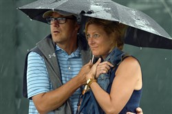 Andy and Ashley Staples of Phoenix, Ariz., wait out a rain delay Thursday on the 17th hole at Oakmont Country Club. Play during the first round of the U.S. Open was suspended twice by the weather.