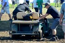 Grounds crew members try to free a cart from the mud Friday at the 16th U.S. Open at Oakmont Country Club.