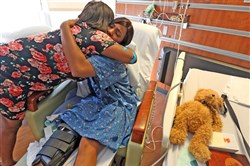 Tiara Parker, left, and her friend Patience Carter, both victims in the Pulse nightclub shooting, embrace as they share a moment at in Carter's Florida Hospital Room before they meet President Barack Obama on Thursday.