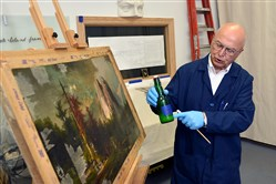 Boris Brindar talks about some of the chemicals used in restoration as he works on a large oil painting.