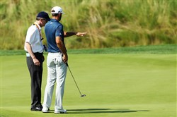 Dustin Johnson of the United States chats with a rules official on the fifth green during the final round of the U.S. Open at Oakmont Country Club in Oakmont.