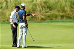 Dustin Johnson  chats with a rules official on the fifth green during the final round of the U.S. Open at Oakmont Country Club.