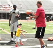 Benjamin Roethlisberger helps his dad, Steelers quarterback Ben Roethlisberger, by tossing him a football during ProFootball Camp on Sunday.