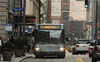 A PAT Bus makes its way along Smithfield Street in downtown Pittsburgh .