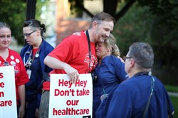 Nurse Shawn Deitz, center, is hugged by a co-worker at 7 a.m. Sunday as she walks out of Abbot Northwestern Hospital in Minneapolis at the end of her shift, joining other nurses on the picket line.