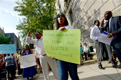 Supporters of the Pittsburgh Public Schools board and their choice of the new superintendent chant before a school board public hearing in front of the administration building in Oakland on Monday.