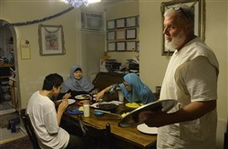 "Phillip Snow, far right, prepares to sit down with his family for their ""Su-hur meal"" before they start their fasting. Behind him, left to right, his son Daniel, 13, his wife, Safiye, and daughter Maysa, 11, in their North Side home overnight Monday before the start of the Ramadan Fasting Solstice."
