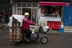 FILE - In this Thursday, Nov. 12, 2015, file photo, a Yihaodian delivery man leaves for his rounds in Shanghai. Wal-Mart said Monday, June 20, 2016, that it was giving JD.com ownership of its Yihaodian e-commerce site in China, including the brand and app. (AP Photo/Ng Han Guan, File)