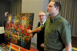 Local artist Johno Presoak, right, invites John Bonassi, Three Rivers Regatta board chairman, and others to touch his painting using sand from last year's Regatta event during a press conference Thursday at Rivers Casino on the North Shore.