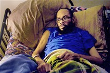 John Ellis, 47, who survived the Wilkinsburg mass shooting on March 9 and is now paralyzed, recalls the attack Friday while lying on his bed at his parents' house. Five people and an unborn child were killed in the shooting.