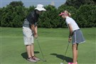 Colm Parrish, who works at Bob O'Connor Golf Course, gives instruction to Jamie Rush of Canonsburg.