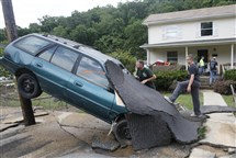 Jay Bennett, left, and stepson Easton Phillips survey damage to a neighbor's car by their home Friday in White Sulphur Springs, W.Va.