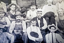 A photograph of an undated handout image of Jack Daniel, center white hat, and to the left, a man who could be a son of Nearis Green.