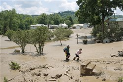People trudge Saturday through mud deposited during flooding of the Elk River along Route 119 in Falling Rock, W.Va., on Saturday.
