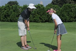Colm Parrish, a volunteer coach at the Bob O'Connor Golf Course, gives instruction to Jamie Rush, 13, of Canonsburg prior to The First Tee of Pittsburgh Tournament on Saturday.