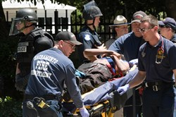 Paramedics rush a stabbing victim away on a gurney Sunday after members of right-wing extremists groups holding a rally outside the California state Capitol building in Sacramento clashed with counterprotesters, authorities said.