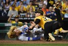 Pirates pitcher Chad Kuhl tags out the Dodgers' Justin Turner Sunday.