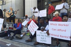 People hold up signs and demonstrate outside City Hall, Monday, June 27, in Oakland, Calif. A scheduled vote in Northern California is expected to decide whether to ban rail shipments of coal over concerns it would pose a public health or safety hazard.
