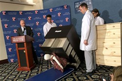 Elliot Kaye, left, chair of the Consumer Product Safety Commission, and CPSC employees watch Tuesday as a 28-pound dummy is crushed under IKEAs Malm-model dresser during a live demonstration at the National Press Club in Washington, D.C. The dresser model is one of the least expensive offerings in IKEA's lineup.
