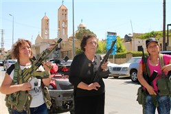 Lebanese Christian women hold weapons as residents of the Christian village of al-Qaa, near Lebanon's border with war-ravaged Syria, secure the area on Tuesday.