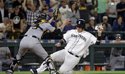 Mariners' Dae-Ho Lee, right, slides toward Pirates catcher Chris Stewart before being tagged out at home during the seventh inning Tuesday in Seattle.