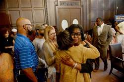 Pittsburgh Public Schools board President Regina Holley hugs retired district employee Cherri Banks after the board Wednesday night voted against rescinding the contract of incoming superintendent Anthony Hamlet, background right.