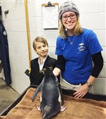Mac Horvath with a penguin at the Pittsburgh Zoo with penguin keeper Jessica.