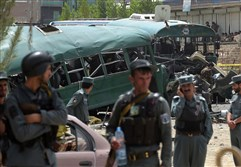 Afghan security personnel gather near the wreckage of buses that were carrying police cadets at the site of a bomb attack on the outskirts of Kabul today. At least 27 policemen were killed and 40 wounded after a bomb attack claimed by the Taliban.