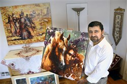 Thar Sayegh with some of his art in his Greenfield home. Thar is originally from Iraq.