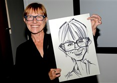 Beth Ann Paul holds a caricature of herself drawn by artist Clarence Butler during a rooftop event supporting the Cancer Caring Center.