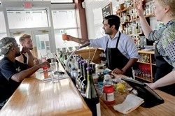 Javid Hashmi, bartender at The Livermore in East Liberty, serves a drink Friday to Brogan McGowan. Seated by Mr. McGowan is Will Tolliver. Emily Sturzebecher stands at right.