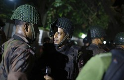 Bangladeshi security personnel stand guard near a restaurant that has reportedly been attacked by unidentified gunmen in Dhaka, Bangladesh. Local media reported that a group of attackers took hostages inside a restaurant frequented by both locals and foreigners in a diplomatic zone in Bangladesh's capital.