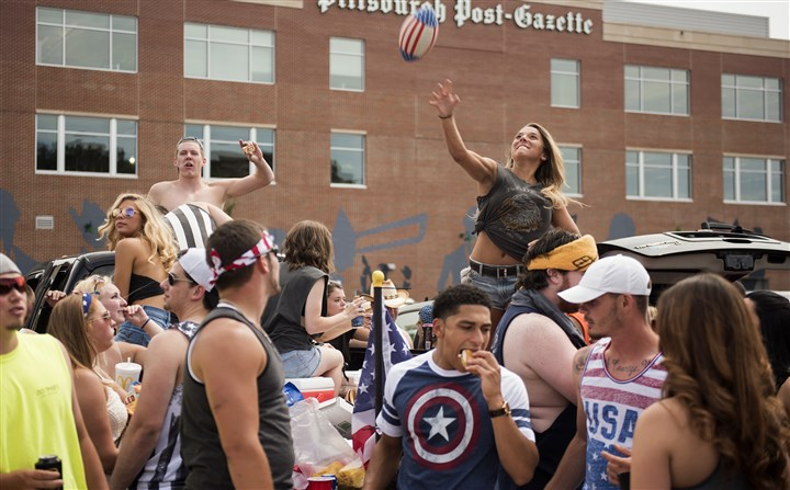 20160702hmnKennyChesney-1 Annie Heisler, 21, of Moon, hurls a football over a crowd tailgating on the North Shore before the Kenny Chesney concert tonight at Heinz Field.