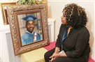Ava Dunn-Shaw looks over a high school graduation photo of her son, Clifford Dunn.