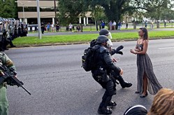 A protester is grabbed by police officers in riot gear after she refused to leave the motorway in front of the Baton Rouge Police Department headquarters on Saturday in Baton Rouge, La. Several hundred protesters, including members of the New Black Panther Party, blocked the roadway, causing police to close the road and move the crowd with riot police. Several protesters were arrested.