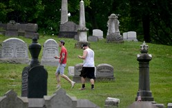 Jon Moorey, left, and ErikTuomisto, both of Lawrenceville, play Pokemon Go on July 13 in Pittsburgh's Allegheny Cemetery.