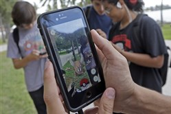 A Pokemon, is found by a group of Pokemon Go players at Bayfront Park in downtown Miami.