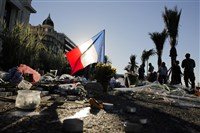 A French flag stands stall in a floral tribute for the victims killed during a deadly attack, on the famed Boulevard des Anglais in Nice, southern France, Sunday.