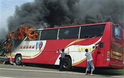 A policeman and another man try to break the windows of a burning tour bus on the side of a highway in Taoyuan, Taiwan, today. The tour bus carrying visitors from China burst into flames on a busy highway, killing more than 20 people on board, officials said.